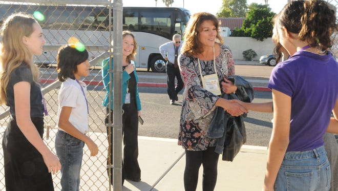 Aspire Academy eighth- grader Abigail Naranjo-Dahlgren welcomes  Kim Watterson, a participant in the National Association of Gifted Children conference, to her school in Tempe.