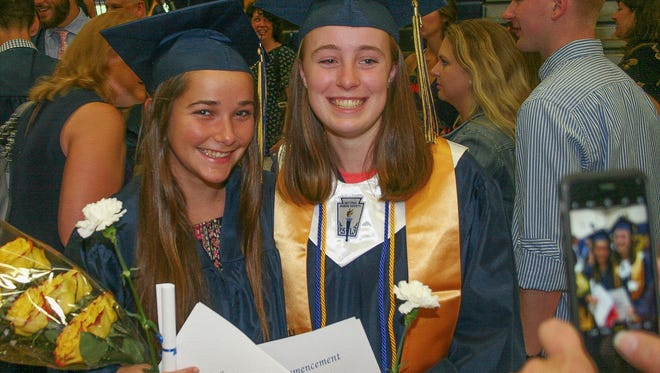 Hannah Deckert (left) and Mary Nugent smile the smiles of brand-new alumni.