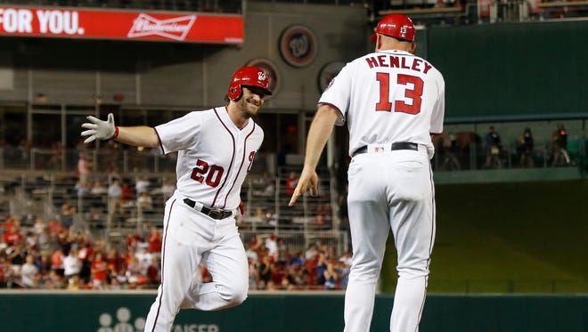 Washington Nationals second baseman Daniel Murphy (20) celebrates with third base coach Bob Henley (13) while rounding the bases after hitting a two-run home run against the New York Mets in the eighth inning at Nationals Park. The Nationals won 4-2.