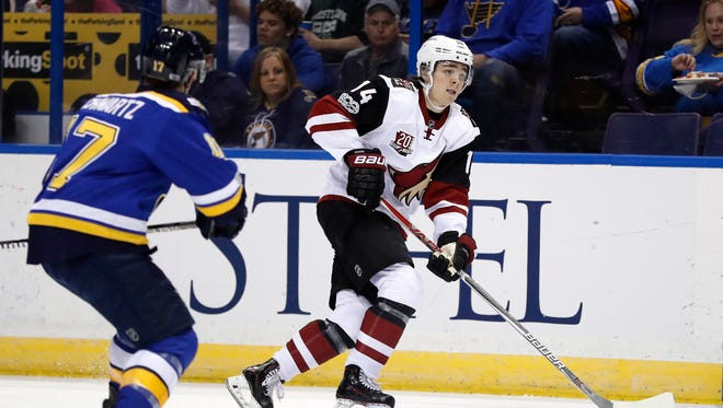 Arizona Coyotes' Clayton Keller (14) handles the puck as St. Louis Blues' Jaden Schwartz watches during the first period of an NHL hockey game, Monday, March 27, 2017, in St. Louis.
