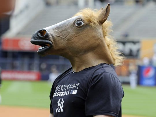 New York Yankees pitcher Shawn Kelley came out to stretch with a horse head mask on before a baseball game against the Chicago White Sox Saturday, Aug. 23, 2014, at Yankee Stadium in New York.