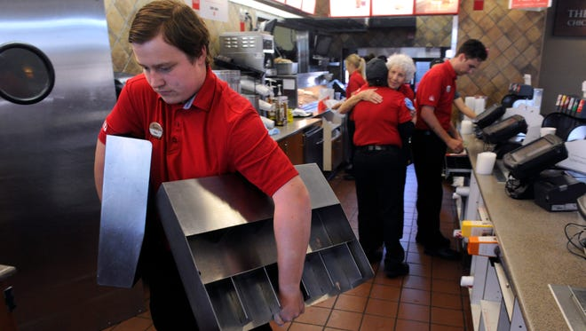 Riley Fisher carries metal shelving out of Chick-fil-A on Southwest Drive Wednesday July 19, 2017 as other staff say their goodbyes in the background. The restaurant will close for four to six weeks as the kitchen is remodeled.