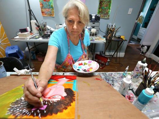 Dawna Magliacano, a local artist, works on a whimsical