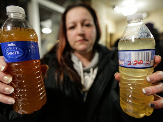 LeeAnne Walters, 36, of Flint, Mich., shows water samples