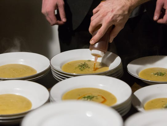 Red lentil and kobacha squash soup gets plated during