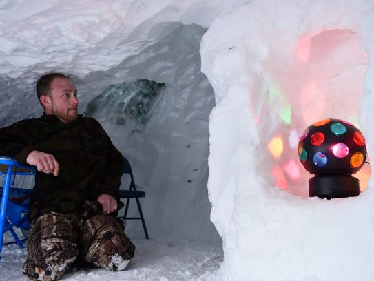 Skyler Cosey watches TV in snow cave he built in his