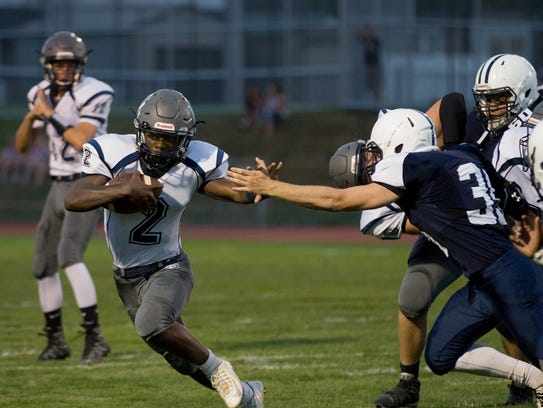 Dallastown running back Zion DeVance pushes off a West