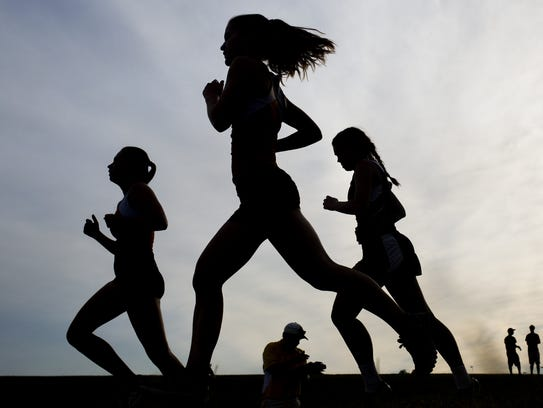 A trio of runners compete during a race featuring runners