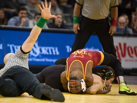 Iowa's Thomas Gilman twists Iowa State's Markus Simmons,