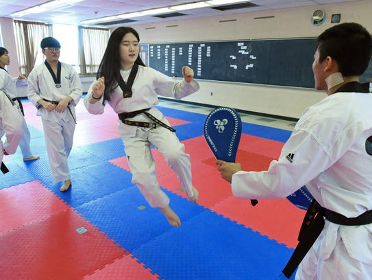Black belt Juliet Lee, center, does kicking exercises