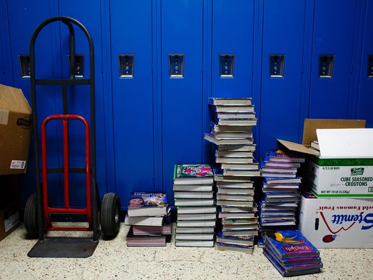 Textbooks that are only a few years old sit stacked