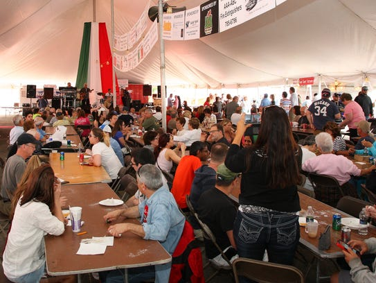 A packed tent of people enjoy the food and music at