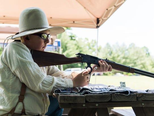 Devyn Mentink, 12, unloads his gun after participating
