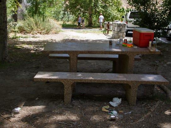 Trash lies on the ground next to a picnic table at