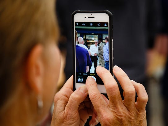 People photograph Apple CEO Tim Cook during a visit