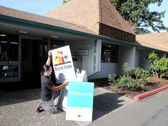 Kitsap Regional Library assistant Rogerick Anas changes the reader board outside of the system's Silverdale branch.