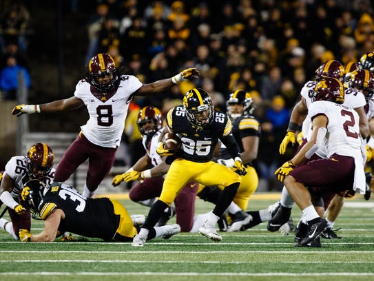 Iowa's Akrum Wadley (25) rushes during their football