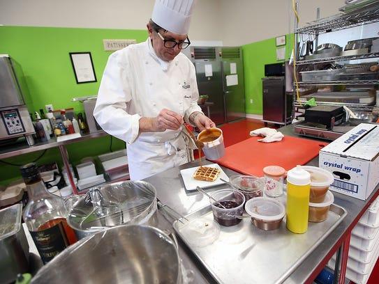 Chef Tamas Ronyai tops a waffle with homemade caramel sauce.