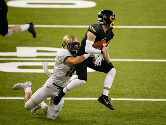 Bettendorf's Carter Bell (11) is tackled by Iowa City,