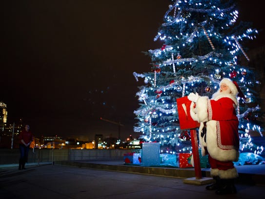 Santa Claus makes a few comments as he lights the Christmas
