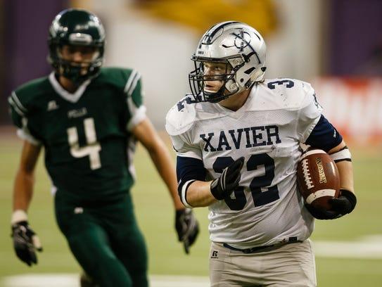 Xavier, Cedar Rapids' Joey Drahozal (32) runs in to