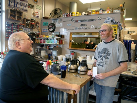 Craig Kenady, right, co-owner of That One Place in Port Orchard, visits with daily customer Dean Sanders. Kenady and his wife, Evaline, opened a restaurant during the recession.