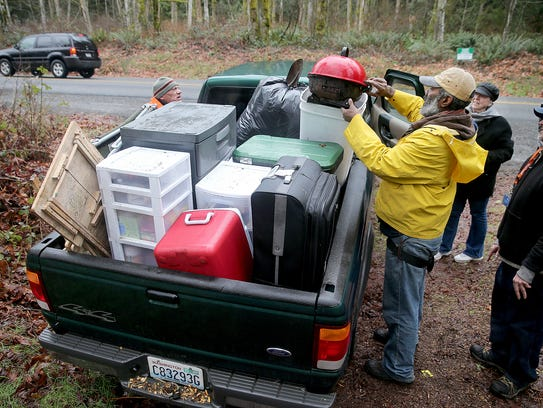 Gerald Harris and Dan Crawford load a pickup truck at the homeless camp on Almira Drive in East Bremerton on Thursday. Some of the belongings will be taken to a storage unit that was donated to residents of the camp.