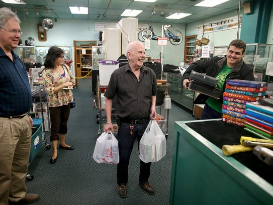 Dick Maurice, owner of Callow Pawn & Jewelry, carries out an order for a customer Gabrial Harinshfeger. Maurice is closing the pawn shop and retiring on Friday.