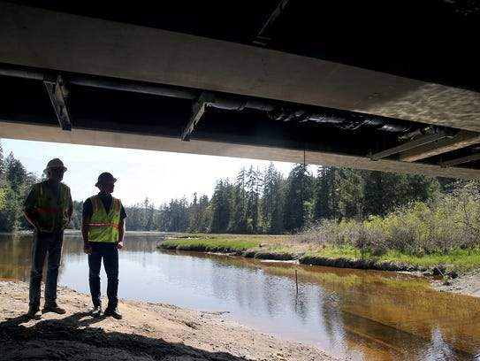 Redside Construction site supervisor Dan Rosler, left, and owner Sam Berry look at the underside of the new West Kingston Road bridge on Thursday. The bridge is slated to open by Monday.