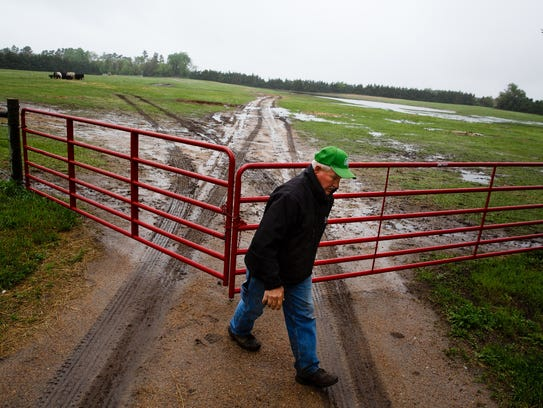 Farmer and Ranchers Ron Crumly closes a gate to a cow