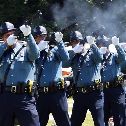 Arkansas State Police troopers fire a 21-gun salute