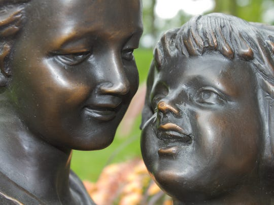 Mother and child share the wonder of a new book in a sculpture installed east of the Howell Carnegie District Library in memory of volunteer Mary Lou Annatoyn.