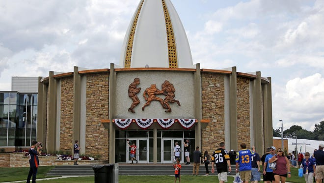 FILE - In this Aug. 5, 2017, file photo, football fans toss footballs on the lawn outside the Pro Football Hall of Fame in Canton. The 2020 enshrinement ceremony and preseason game have been canceled.