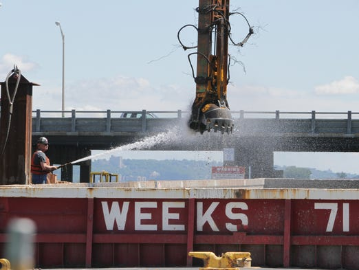 A worker hoses off a clamshell bucket used in the placement of pilings at the Tappan Zee Bridge construction project June 5, 2014.