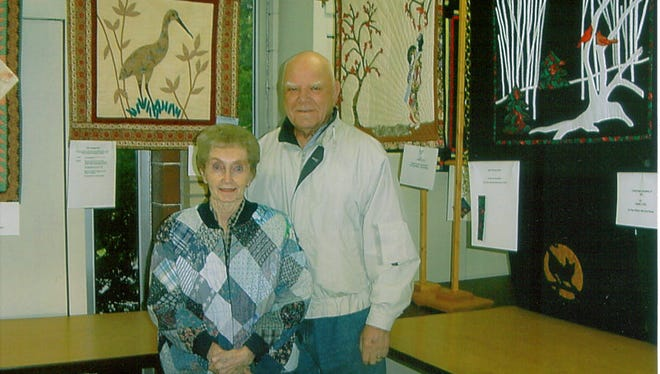 Connie Lutes, shown with her late husband, Bob, displays some of her Challenge Quilts. Lutes will be honored by the Hill 'N Hollow Quilters Guild in October.