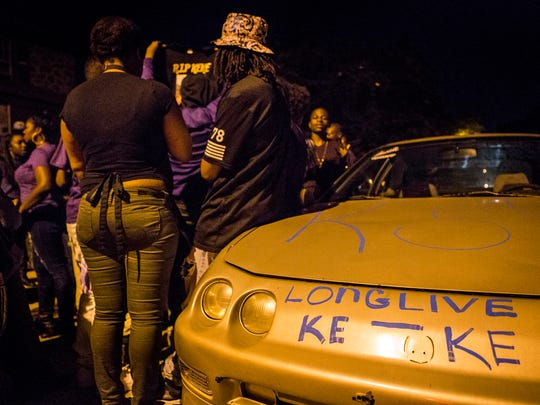"""Friends of Keshall """"KeKe"""" Anderson stand next to a car with supportive messages for Anderson at a vigil commemorating what would have been her 20th birthday on Thursday night. Anderson was shot and killed along W. 20th Street in Wilmington on September 18th."""