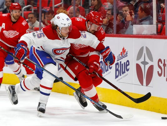 Montreal Canadiens left wing Jacob de la Rose (25) and Detroit Red Wings defenseman Xavier Ouellet (61) battle for the puck in the third period of an NHL hockey game Thursday, Nov. 30, 2017, in Detroit. (AP Photo/Paul Sancya)