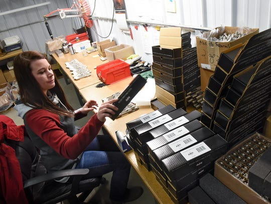 Emily Funk assembles parts at Alex Pro Firearms Friday,