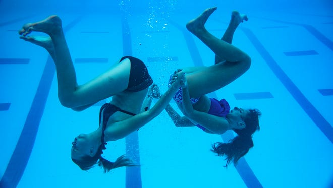 Synchronized swimmers Michaela McKiernan, 14, and Rhiannon Johnston, 13, practice a complicated move during practice on Tuesday, July 12.