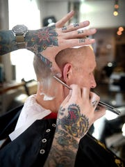 The Black Comb Barbershop at 31 E. Orange Street in Lancaster has just moved around the corner, providing classic services. Barber Jon Leitzel still uses a straight razor on his clients. Tom Gehrke is treated to a beer during his mid afternoon cut.