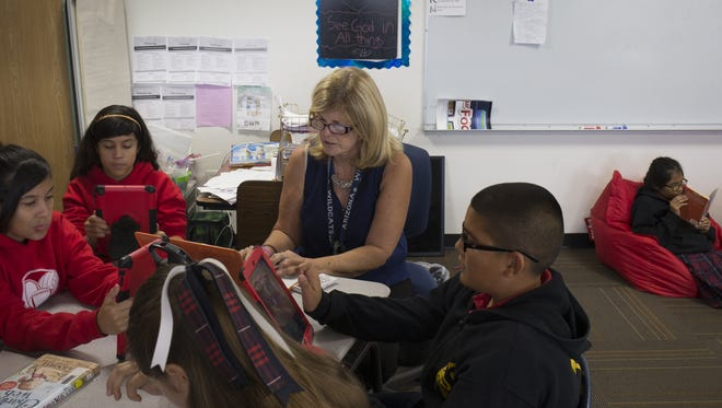 Language arts teacher Isabel Bickman (center) works with students on October 28, 2015, in their 5th grade classroom at St. John Vianney Catholic School, 539 E La Pasada Blvd., Goodyear.