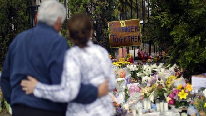 A couple embrace near a growing memorial across the street from the Chabad of Poway synagogue in Poway, Calif., in April 2019. A 19-year-old gunman opened fire as about 100 people were worshiping exactly six months after a mass shooting in a Pittsburgh synagogue.