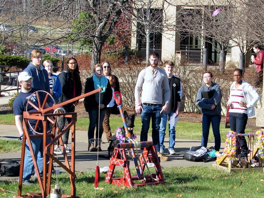Participants watch as a catapult launches a water balloon