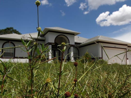 The Bonita Springs home of Mark and Teresa Sievers has a yard full of overgrown weeds and tall grass.