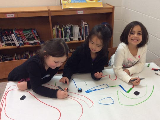 Students work in teams to program Ozobots using colored line sequences.