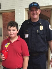 Jayden Valdez, a student at Paul Breaux Middle, meets with Lafayette Fire Department Capt. Reggie Patin at the school's college and career day Thursday.
