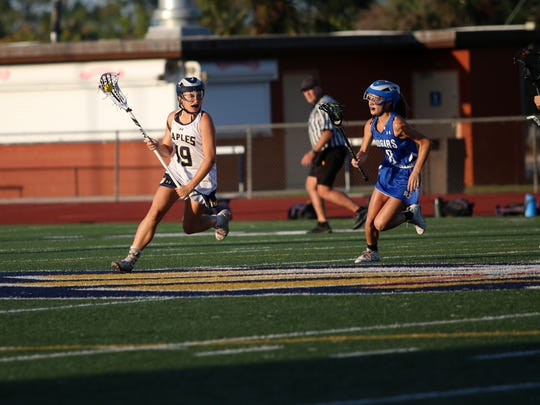 Naples sophomore Sophie Sullinger (19) runs up the field during the District 20 Girls Lacrosse Championship between rivals Barron Collier and Naples at Staver Field on Thursday, April 19, 2018.