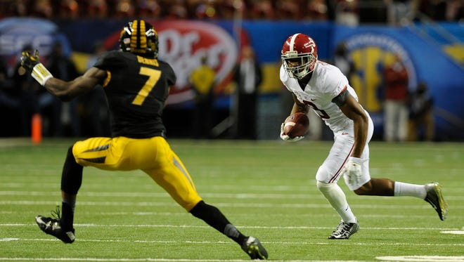Alabama wide receiver Amari Cooper (9) carries against Missouri defensive back Kenya Dennis at the SEC Championship Game in the Georgia Dome in Atlanta, Ga. on Saturday December 6, 2014.