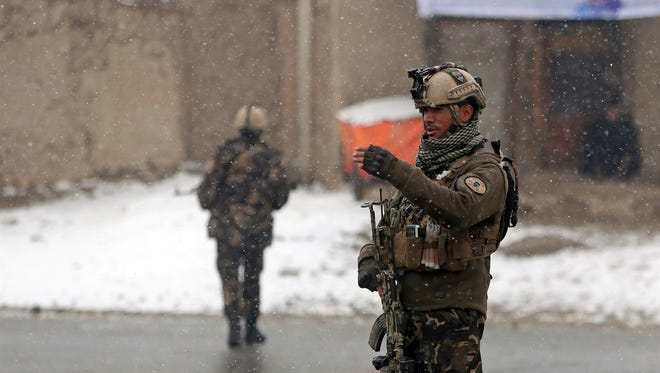 Afghan security personnel stand guard at the site of an attack at the Marshal Fahim academy in Kabul, Afghanistan Monday, Jan. 29, 2018.