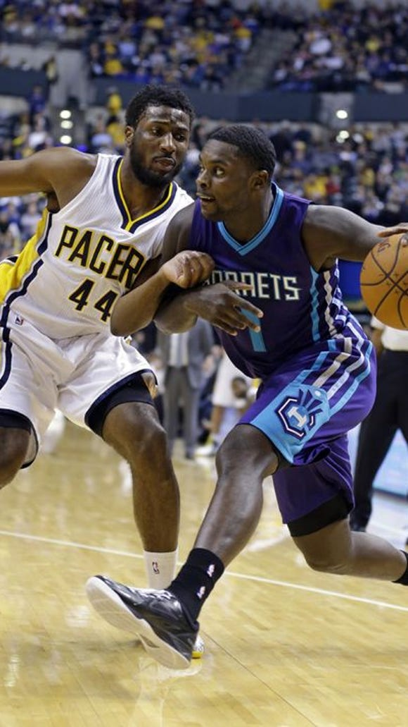 Charlotte Hornets guard Lance Stephenson, right, drives on Indiana Pacers forward Solomon Hill during the first half of an NBA basketball game in Indianapolis, Wednesday, Nov. 19, 2014. (AP Photo/Michael Conroy)
